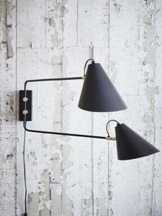 This elegant, double arm wall light is made from iron with brass accents. Its arms are adjustable to provide light wherever you may need it. Height: 28cm, Length: 35-55cm