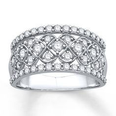 A lacy pattern embellished with sparkling round diamonds flows through the center row of this lovely ring for her. Additional rows of round diamonds above and below complete the look. Styled in 14K white gold with delicate milgrain detail, the ring has a total diamond weight of 1 carat. Diamond Total Carat Weight may range from .95 - 1.11 carats.