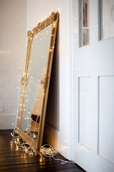 I have a new addiction a need for using Christmas Lights.  large mirror + white christmas lights