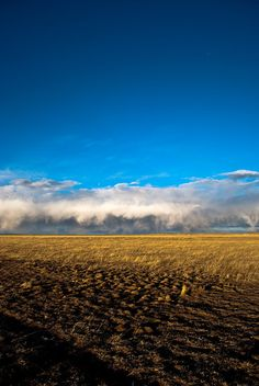 Early-spring storm clouds contrast against blue skies and a dry earth, just outside the small town of Wellington, Colorado.    This photo comes