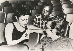 Elis Regina, Milton Nascimento e o Maestro Rogério Duprat sentados em um auditório.