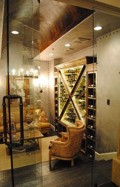 Wine cellar has a living room built in with a clear glass wall and furniture to relax and entertain guests with during tasting parties.
