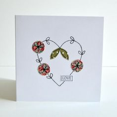 A lovely delicately handmade embroidered heart greetings card decorated with pretty fabric flowers and leaves and the word love. Suitable for various occasions, Valentines Day, Wedding Anniversary, Wedding Congratulations, Engagement or any other special occasion. Stitched using