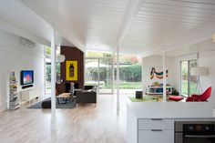 """The living spaces of house, built in 1972 or 1973, were originally divided into three—a kitchen, living and dining area, and an atrium (previous owners had covered the atrium with a roof). """"The new owners wanted the interior space to flow as one, so we removed the glass doors and solid walls separating the enclosed atrium from the kitchen and living room,"""" principal John Klopf says. """"Some structural posts needed to remain to hold up the roof, but overall the space was opened up almost…"""