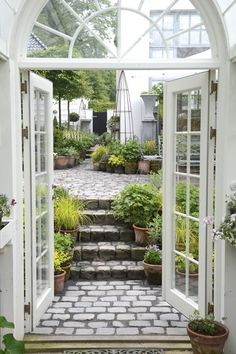 Pots, lots of pots and lovely stone and entering the garden / outdoor room through stunning french doors... Ah, to dream...
