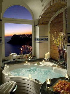 Luxury bathroom/spas....love all of the white candles & the view is absolutely gorgeous!