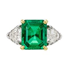 Colombian emerald and diamond dress ring, centering on an octagonal-shaped step-cut emerald weighing 3.49 carats, flanked by two calf head-shaped diamond shoulders, mounted in platinum with an 18k yellow gold basket, signed Fred Leighton.