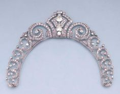 AN ART DECO DIAMOND TIARA/NECKLACE -- Of openwork design, the central detachable geometric panel set with old-cut diamonds and nine paste baguettes to the graduated diamond scroll and collet sides, tiara fittings deficient, fittings to wear tiara as a necklace and central panel as a brooch, circa 1930s.