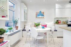 weiße Küche mit kleinem Essplatz und Sitzbank