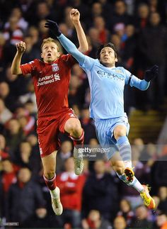 Lucas Leiva of Liverpool goes up with David Silva of Manchester City during a Barclays Premier...