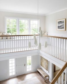 A honey stained staircase rail is fitted to white spindles lit by a Fontaine Vertical Chandelier, as a white built-in bench sits on a second floor landing beneath a window. White Wainscoting, House, Landing Decor, Home, Countryside House, Beach House Kitchens, White Shiplap Wall, Custom Furniture Design, White Staircase