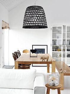 Casually elegant modern dining room with a black basket-style pendant lamp and sleek wood furniture. #design #homedecor #modern