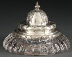 """A TIFFANY & CO STERLING SILVER AND CUT GLASS INKWELL, CIRCA 1900. The hinged onion domed cover with repoussed floral rosettes and finial lifting to reveal a secondary hinged well cap with silver surround atop a wide flaring lobed floriform integral crystal base cut with floral rosettes and palms. Marked """"Tiffany & Co. 11680 makers 4933 sterling silver C"""". Sold for $12,000"""