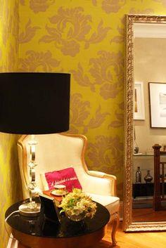 O papel de parede com estampa floral na cor lima (Wallpaper) é o destaque na parede do Hall Superior, projeto das designers de interiores Selma Milaré Rubim e Solange Vieira Rubim. A moldura dourada e imponente do espelho apoiado no chão, da Moldura Minuto, completa a ambientação.