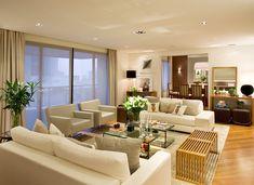 Living moderno integrado com sala de jantar! Os sofás levam tecidos claros, e o restante do mobiliário madeira e vidro. O tapete é da Vitrine!
