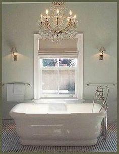 Gold chandelier in white bathroom