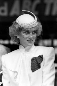 Diana, Princess of Wales, dressed in a veiled hat and matching outfit by designer Bruce Oldfield,…