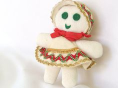 This darling vintage girl Christmas ornament is a Scandinavian style gingerbread girl. The soft, stuffed ornament is made from 1970s white double knit. fabric. Possibly handmade.  With Scandinavian styling, the gingerbread girl is wearing a tent dress and bonnet tie with a red ribbon and trimmed in red, green and gold rick rack and trim. She has green die cut felt eyes and mouth. There is a nylon hanging loop I added since the original was gone.  She is 4.25 inches (10.8 cm) tall, not…