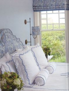 Lovely blue and white bed linens, as well as a wonderful headboard