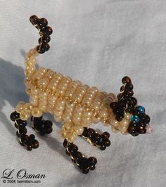 A 3D siamese cat sculpted with wire and seed beads