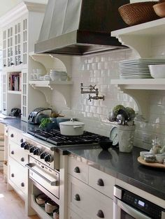 Kitchen inspiration: subway tile, dark stove hood, dark countertop, shelving over cabinets