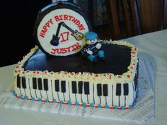 Created by Catharine's Cakes - Musical Birthday Cake. Fondant piano, drum and musician.