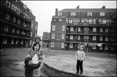 Clown visiting Vauxhall housing estate, London, England, 1973, photograph by Robert McFarlane.