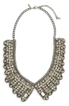 Dazzling crystals light up the feather-shaped scallops of a striking statement necklace.