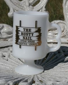 The Rusty Nail Steak House and Cocktail Lounge.   White milk glass with gold decoration.   Marked USA on underside. Footed. Approximately 4 3/4 inches tall.   Fun vintage restaurant mug.   At time of listing, I have 2 of these. Buy one, or buy both and save on shipping.