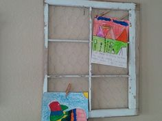Old window frame with chicken wire on the back, and kids artwork hung on it!