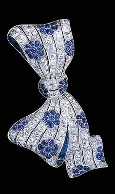 A FINE SAPPHIRE AND DIAMOND BOW BROOCH Designed as diamond openwork lines with cabochon-cut sapphire flowerheads set at intervals to the french-cut sapphire edge detail, circa 1924 Bow Jewelry, Art Deco Jewelry, Jewelry Design, Fashion Jewelry, Diamond Bows, Diamond Brooch, Sapphire Diamond, Blue Sapphire, Sapphire Bracelet