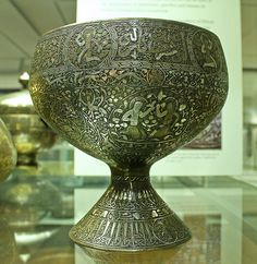 Cup on high foot    Cup on high foot, engraved with inscriptions and figurative and floral designs. It is made of high tin bronze and inlaid with silver.  Iran, 14th century AD