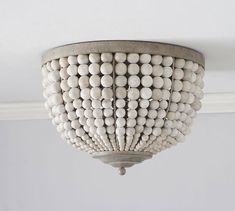 Leila Beaded Flushmount This light fixture has the appeal of a vintage found piece, with neutral-toned wood beads and a rustic hand-applied gray wash on the metal accents.