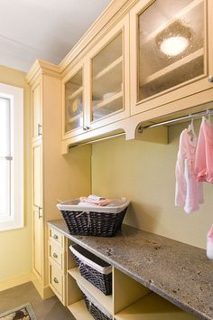 Sunny yellow laundry room with ample storage and space designed by In Detail Let's think