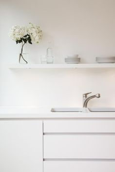 """The whiteness of the bespoke kitchen units was matched by a pure white Corian work surface and Corian shelves,"""" Holland says. """"There is no conventional back splash: An acrylic sealer has been applied to the paint work, which will require refreshing periodically, subject to damage.""""Remodelista-Hackett-Holland-Notting-Hill-kitchen-extension"""