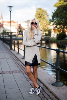 Ellen Claesson is wearing a long knit grey jumper and black skirt from Zara and shoes from Converse