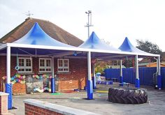 3 peaked blue Cube canopies providing shade for a school playground.
