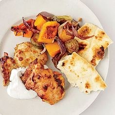 """""""Chicken might be my overall favorite meat for feeding a crowd,"""" Kristin Kimball says. She sometimes roasts it with Indian spices she picks up on her biannual trips to Manhattan—like the curry in this one-pan recipe of yogurt-marinated chicken with butternut squash and brussels sprouts."""