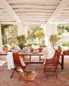 un mobilier en bois et un carrelage de couleur terre cuite sur la terrasse