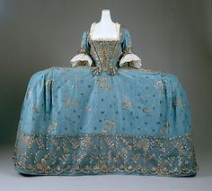 Court Dress, ca. 1750. British, silk, metallic thread. Universally described as the robe à la française, In its most formal configuration, it presented a wide and flattened profile accomplished by enlarged panniers. Constructed of supple bent wands of willow or whalebone and covered in linen, panniers took on broader or narrower silhouettes. The most remarkable held out the skirts like sandwich boards, barely wider than the body in side view but as expansive as possible in front or rear view.