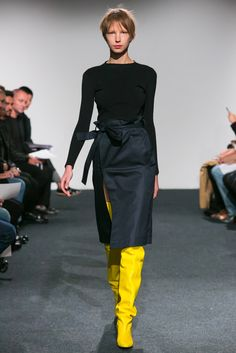 Spring 2015 Ready-to-Wear - Vetements -- black knit long-sleeve boat neck top with crisp black wrap shirt and birght yellow thigh high boots.