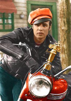 マーロン・ブランド(Marlon Brando)乱暴者1953   1924年4月3日 - 2004年7月1日    マーロン・ブランドマーロン・ブランド銀幕スター彩色写真館 カラー化画像  マーロン・ブランドはこの映画で反抗的な若者を演じます。 ブランドのファッションは革ジャン、ジーンズ、Tシャツ、ブーツ、と今では取り立てて何でもないような服装ですが、当時としては作業着であるジーパン、下着であるTシャツを着こなしバイクにまたがる姿が、反体制的な50年代当時の若者に受け、革命的なファッションとなります。以降の若者ファッションとして定着、それが今日まで続いているのですからジーンズ会社はマーロン・ブランドと、あとに続くジェームズ・ディーンに足を向けて寝れません。