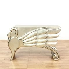 This art deco style console table is featured in a wood with a shiny antiqued silver finish. This accent table has an elegant carved swan decal with swooping organic lines and curved edges. Perfect sofa table for catching eyes! #contemporary #tables #consoletable #sandiegovintage #vintagefurniture
