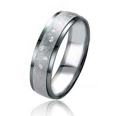 Alliance Élya en or blanc et or gris d'une largeur de 5,4 mm et avec 5 diamants. Cette alliance fait partie de la famille Black & White et elle est disponible au prix de 700 euros.