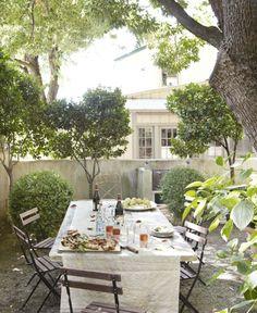 Dining al fresco in a walled garden - European garden - Outdoor bistro table with white tablecloth