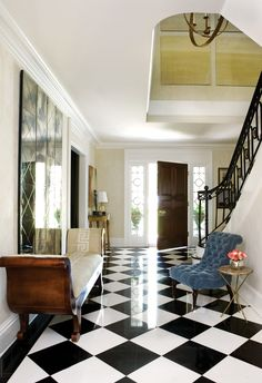 Inspired by the architectural stairwell and black-and-white marble floor, Christy Dillard   created an entryway with Neoclassical glamour and ample charm. Using a large-format, hand-stenciled damask wallpaper as her foundation, Dillard mixed materials and textures with uncompromising ingenuity.