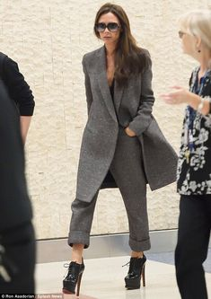 Fashionista mother: Showcasing her immaculate and on-point travel-chic style, the former pop star donned a grey speckled overcoat and matching high-waisted, turn-up, three-quarter-length trousers