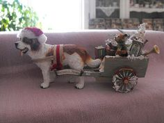 dollhouse miniature St. Bernard wearing a Santa hat and pulling a cart filled with toys