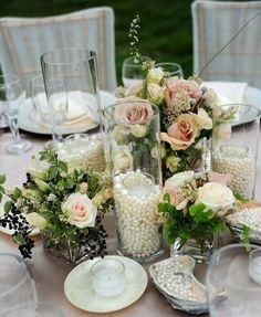 Jarrones rellenos de perlas con velas para centros de mesa de bodas vintage. #BodasVintage