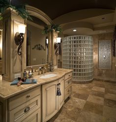 Master bathroom with a tile floor, a glass block shower wall, a very large vanity we would all love to have and plenty of luxurious space. #glassblocks #showers